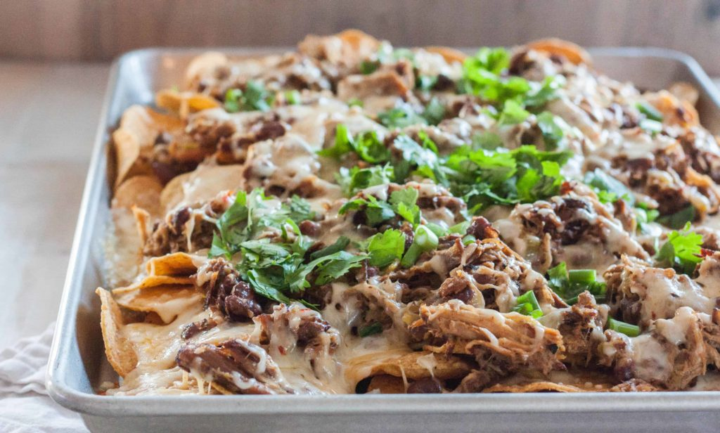 the best nachos - nachos with pulled pork pinto beans green chiles and two cheeses